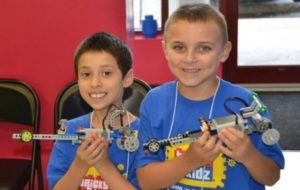 Boys holding dragster models in our workshops and programs with lego®